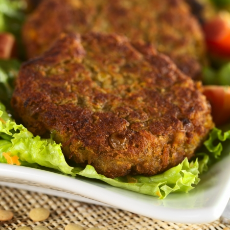 veggies: Vegetarian lentil burger made of brown lentils and grated carrots served on lettuce (Selective Focus, Focus on the front of the first burger) Stock Photo