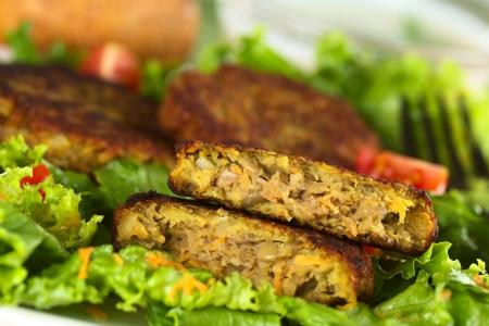 lentejas: Hamburguesa vegetariana hecha de lentejas lentejas y zanahorias ralladas que se presentan en la lechuga (foco selectivo, foco en la hamburguesa mitad superior) Foto de archivo