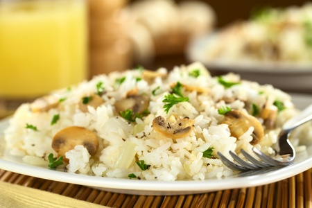 Mushroom risotto with parsley (Selective Focus, Focus on the front of the mushroom slice one third into the dish)