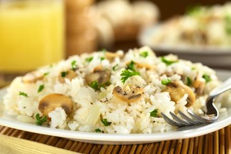 Risotto aux champignons avec le persil (au point sélective, Focus sur l'avant de la tranche de champignon tiers dans le plat)