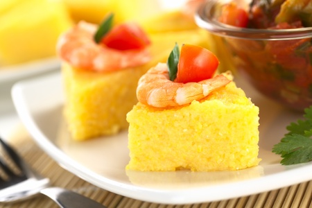 polenta: Polenta slices with shrimp and cherry tomato accompanied by hogao, a Colombian sauce made of tomato, onion and cilantro (Selective Focus, Focus on the front of the shrimp)  Stock Photo