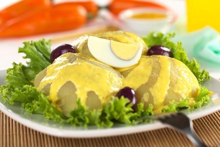 Apéritif péruvien appelé Papa a la Huancaína fait de pommes de terre cuites, la sauce huancaina, ?ufs durs et des olives (sélective focus, Zoom sur l'oeuf)