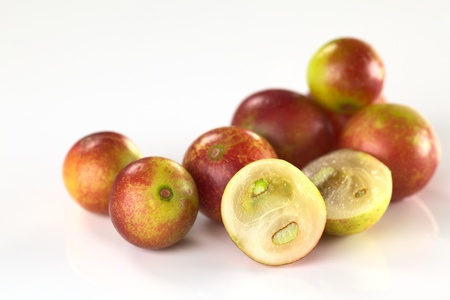 Camu camu berry fruits (lat. Myrciaria dubia) which are grown in the Amazon region and have a very high Vitamin C content (Selective Focus, Focus on the half camu camu in the front and the the complete berry to the left of it)