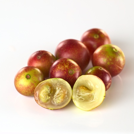 Camu camu berry fruits (lat. Myrciaria dubia) which are grown in the Amazon region and have a very high Vitamin C content (Selective Focus, Focus on the camu camu halves in the front) Stock Photo