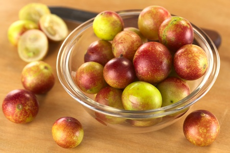 Camu camu berry fruits (lat. Myrciaria dubia) which are grown in the Amazon region and have a very high Vitamin C content (Selective Focus, Focus on the berries in the middle of the bowl) Stock Photo