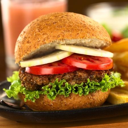 lentejas: Hamburguesa vegetariana de lentejas en bollo de trigo integral con lechuga, tomate y pepino (Enfoque, Enfoque en la parte delantera del sándwich) Foto de archivo