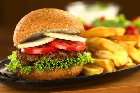 lenteja: Hamburguesa vegetariana de lentejas en bollo de trigo integral con lechuga, tomate y pepino acompa�ados de papas a la francesa (Enfoque, Enfoque en la parte delantera del s�ndwich) Foto de archivo
