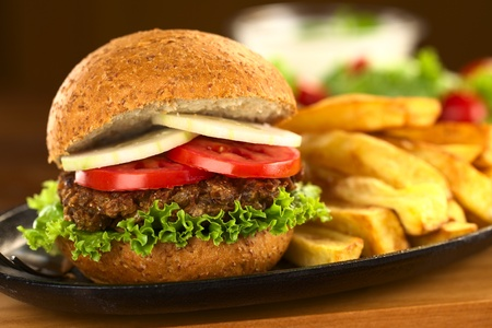 vegetarian hamburger: Vegetarian lentil burger in wholewheat bun with lettuce, tomato and cucumber accompanied by French fries (Selective Focus, Focus on the front of the sandwich)