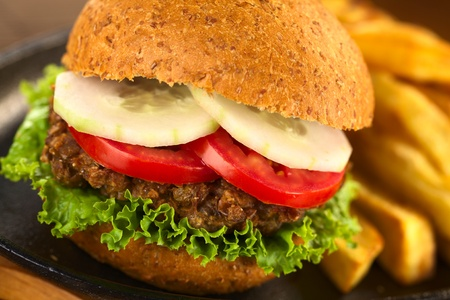 lentil: Vegetarian lentil burger in wholewheat bun with lettuce, tomato and cucumber accompanied by French fries (Selective Focus, Focus on the front of the lettuce, lentil burger, tomato and cucumber)