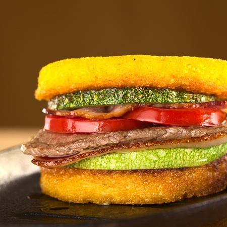 polenta: Polenta burger with fried zucchini, bacon, beef and tomato (Selective Focus, Focus on the front of the burger)