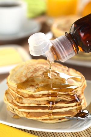 Pouring maple syrup on fresh homemade pancakes (Selective Focus, Focus on the front of the upper three pancakes) photo