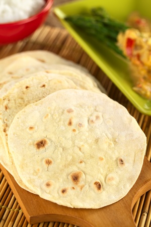 Indian flatbread called chapati on wooden board (Selective Focus, Focus on the big brown spot on the left) Stock Photo