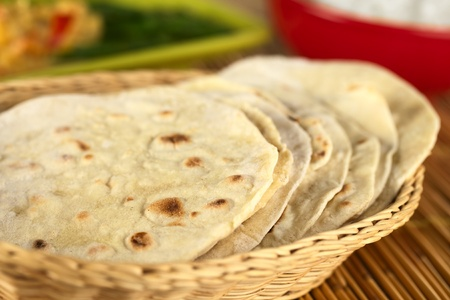Indian flatbread called chapati in basket (Selective Focus, Focus on the big brown spot on the front of the first chapati) photo