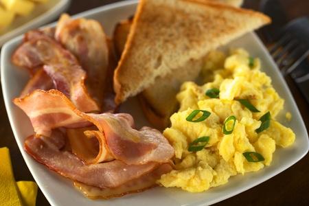 scrambled eggs: Tocino frito ad huevos revueltos con pan tostado (Enfoque, Enfoque en la parte inferior de la panceta y huevo)