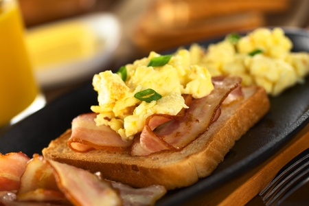 bacon and eggs: Fried bacon and scrambled egg on toast bread (Selective Focus, Focus on the front of the shallot in the front)