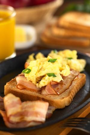 scrambled eggs: De tocino frito y huevos revueltos con pan tostado (Enfoque, Enfoque en la parte delantera de la chalota en la parte delantera)