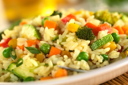 risotto: Vegetable risotto made of zucchini, pea, carrot, red bell pepper, broccoli and pumpkin (Selective Focus, Focus in the middle of the image)  Stock Photo