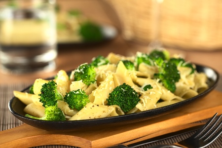 Baked broccoli and pasta with melted cheese and ground pepper on top (Selective Focus, Focus one third into the image)