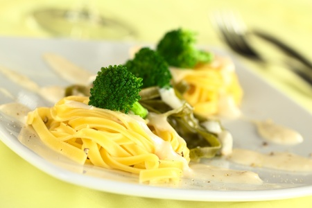 Broccoli florets on yellow and green fettuccine with bechamel sauce and ground pepper (Selective Focus, Focus on the front of the first broccoli floret) Stock Photo - 11735904