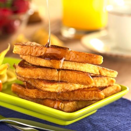 jarabe: Verter el jarabe de arce en el pan franc�s (atenci�n selectiva, hay que centrarse en el frente de la divisi�n superior y el jarabe de correr hacia abajo) Foto de archivo