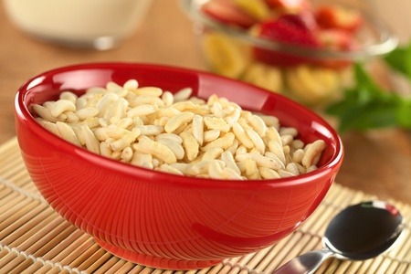 Puffed rice cereal with fruits and milk in the back (Selective Focus, Focus in the middle of the bowl) photo