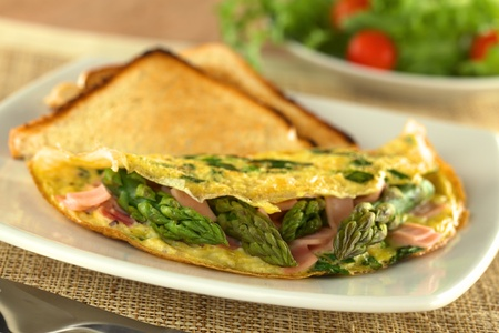 omelet: Green asparagus and ham omelet with toast bread and a fresh salad in the back (Selective Focus, Focus on the three asparagus tips in the front)