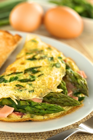 Green asparagus and ham omelet with eggs in the back (Selective Focus, Focus on the asparagus head in the front)