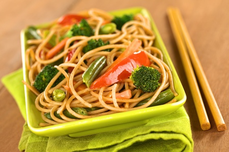 wholemeal: Vegetable and wholewheat spaghetti stir fry with chopsticks (Selective Focus, Focus on the broccoli floret in the front)