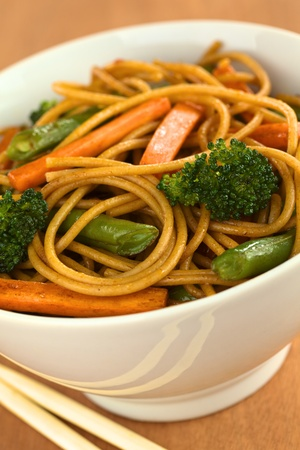 wholemeal: Vegetable and wholewheat spaghetti stir fry in white bowl with chopsticks (Selective Focus, Focus on the broccoli floret on the right)