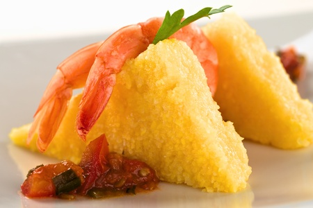 polenta: Polenta slices with cooked shrimp and Colombian hogao sauce (Selective Focus, Focus on the the tail of the first shrimp and part of the sauce below) Stock Photo
