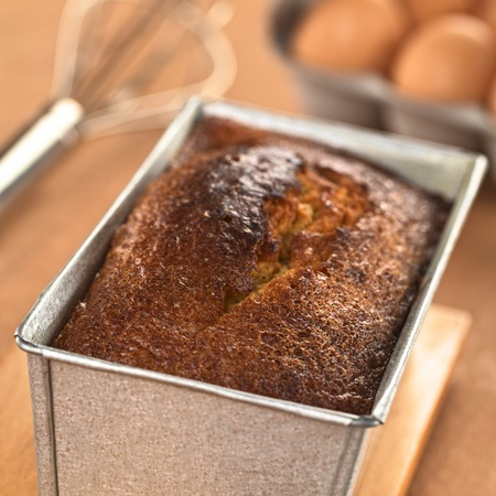 pound cake: Freshly baked pound cake in baking pan with eggs and beater in the back (Selective Focus, Focus one third onto the surface of the cake)