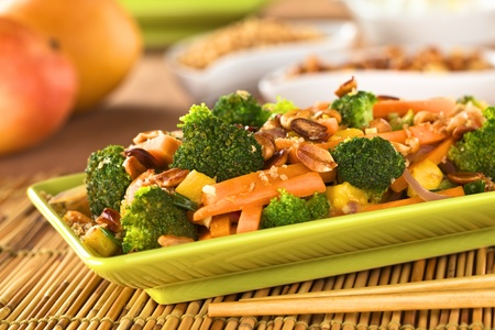 stir fried: Vegetarian stir-fry Thai-style with broccoli, carrot, onion, mango with fried coconut flakes and peanuts  Stock Photo