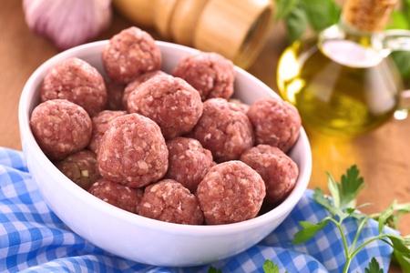carne picada: Raw albóndigas con ajo en un recipiente blanco
