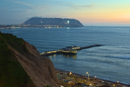 The coastline of Lima, Peru at twilight with the Restaurant La Rosa Nautica reaching into the sea on a pier photo