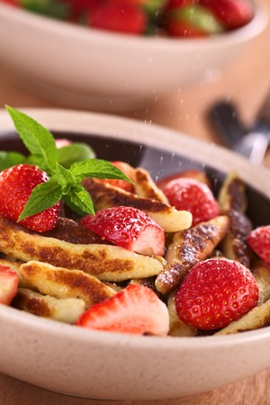 swabian: Schupfnudeln (Swabian potato noodles from Southern Germany) with fresh strawberries, cinnamon and sugar powder (Selective Focus, Focus on the front of the strawberry in the middle of the image and on the tip of the mint)  Stock Photo