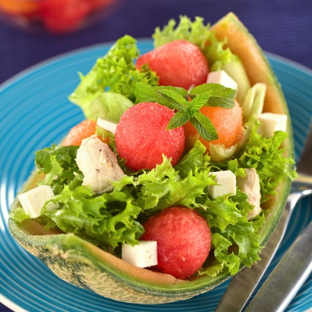 Fresh salad made of watermelon, cantaloupe melon, chicken, cucumber, cheese and lettuce  photo
