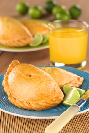 pasty: Peruvian snack called Empanada (pie) filled with chicken and beef served with limes (Selective Focus, Focus on the middle front part of the empanada) Stock Photo