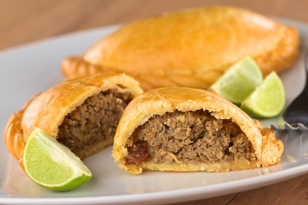 minced pie: Peruvian snack called Empanada (pie) filled with beef and raisin served with limes (Selective Focus, Focus on the empanada stuffing in the front)