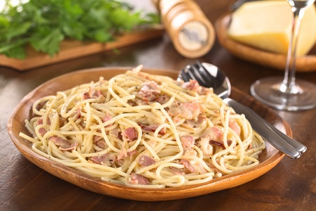 Spaghetti alla Carbonara served on wooden plate (Selective Focus, Focus one third into the meal) Stock Photo