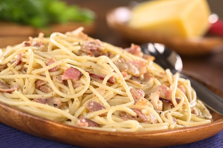 Spaghetti alla Carbonara served on wooden plate (Selective Focus, Focus one third into the meal) photo