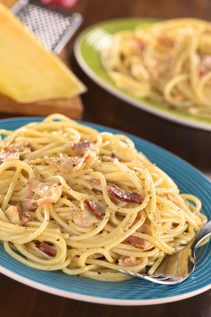Spaghetti alla Carbonara made with bacon, eggs, cheese and black pepper (Selective Focus, Focus one third into the meal) photo