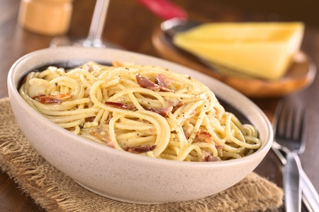 Spaghetti alla Carbonara made with bacon, eggs, cheese and black pepper served in bowl with cheese to grate in the back (Selective Focus, Focus one third into the meal)