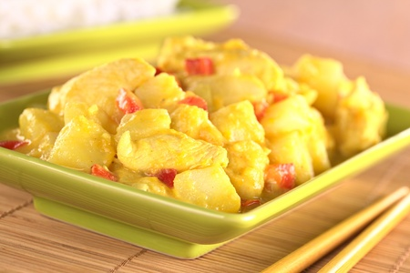 Chicken-mango curry with red bell pepper and potatoes (Selective Focus, Focus on the chicken piece in the front) photo