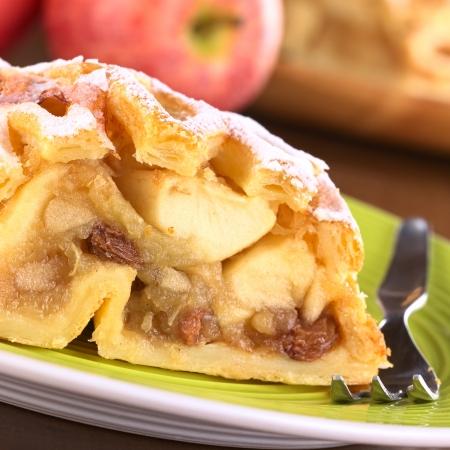 Strudel de manzana con pasas de uva (Enfoque, Enfoque en la pasa en el lado izquierdo de la imagen)
