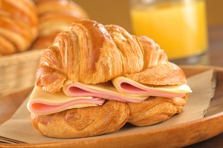 Fresh croissant with ham and cheese on rustic wooden plate with bread basket and juice in the back (Selective Focus, Focus on the ham and cheese slices) photo