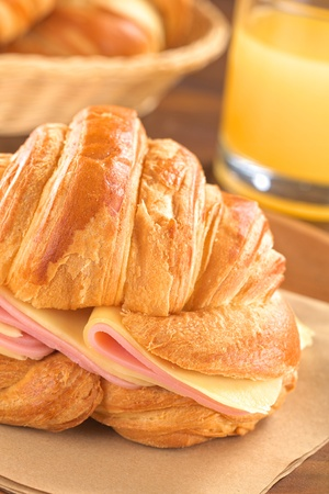 Fresh croissant with ham and cheese slices with juice and bread basket in the back (Selective Focus, Focus on the ham and cheese slices on the right and on the front of the croissant) Stock Photo