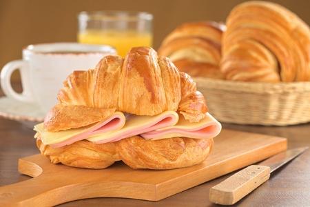 Frais croissants au jambon et fromage sur planche de bois avec du café, jus d'orange et corbeille de pain dans le dos (Mise au point sélective, Concentrez-vous sur le front du croissant et les tranches de jambon et de fromage)