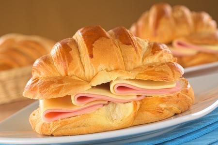 jamon y queso: Croissants frescos con jamón y queso en el plato (Enfoque, Enfoque en la parte delantera del croissant y las lonchas de jamón y queso)