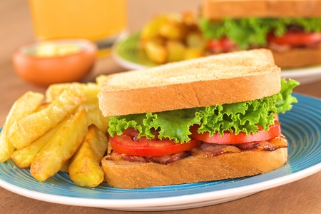 Fresh homemade BLT (bacon lettuce and tomato) sandwich with French fries on plate with juice in the back (Selective Focus, Focus on the front of the sandwich)  photo