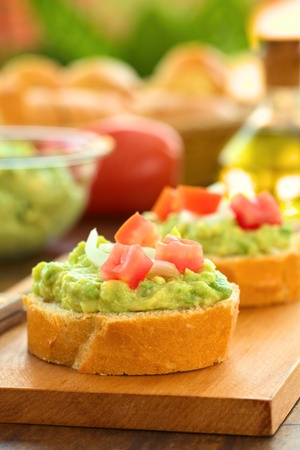 spread: Snack of baguette slices with avocado cream, tomato and onion on wooden cutting board with ingredients in the back  Selective Focus, Focus on the front of the avocado cream on the first baguette slice